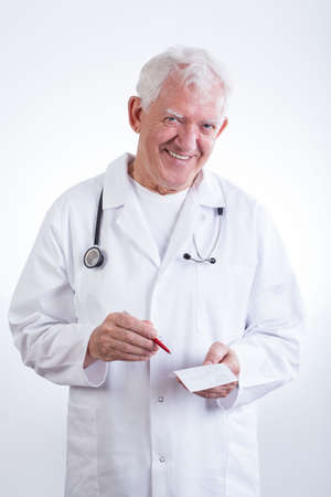 Senior experienced physician writing the prescription photo