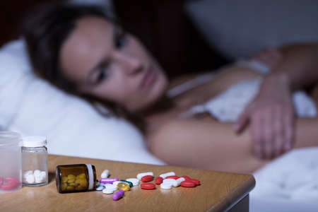 Sleeping pills on bedside table and awake woman