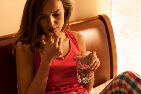 pastillas: Mujer joven en pijama tomando pastillas para dormir
