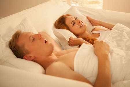 snoring: Snoring man and angry woman lying in bed