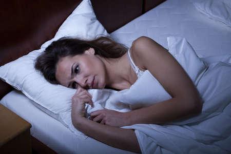 despertarse: Mujer que sufre de insomnio acostado en su cama