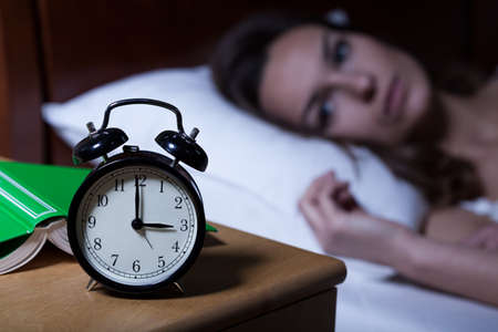 woman clock: Alarm clock on night table showing 3 a.m.