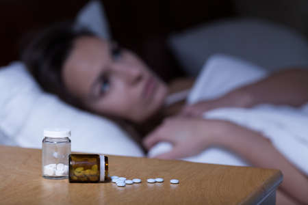 밤 테이블에 누워 수면제와 여자 잠 시도