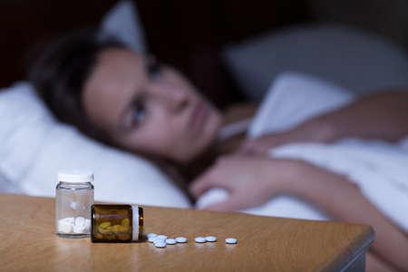 Sleeping pills lying on night table and woman trying to sleep Standard-Bild