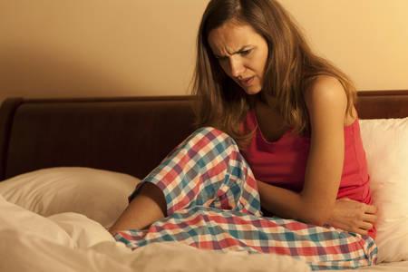 menstruation: Horizontal view of woman in bed having menstruation Stock Photo