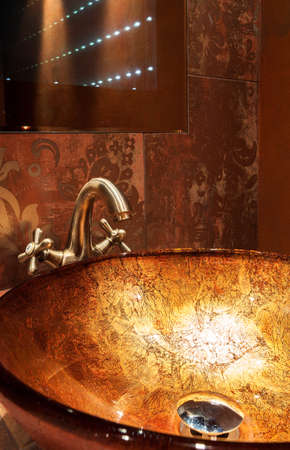View of golden sink in expensive bathroom photo