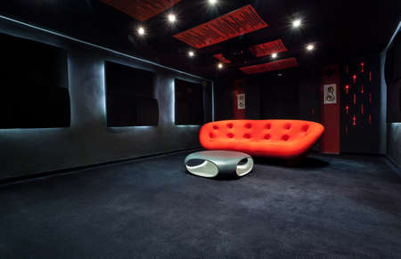 Red modern sofa in dark living room Archivio Fotografico