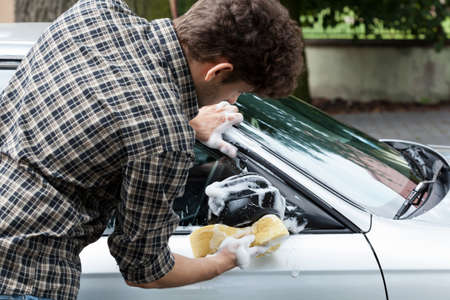 accurately: Young man accurately cleaning wing mirror in his car