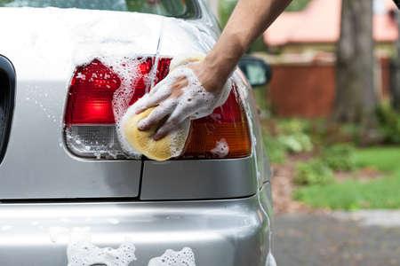 bubble car: Mans hand polishing rear lights of silver car by sponge
