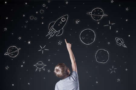 Little boy pointing at drawing sky at night Stock Photo