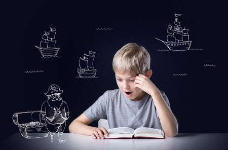 Phantasie des kleinen Jungen beim Lesen der Abenteuerbuch Standard-Bild - 34709124