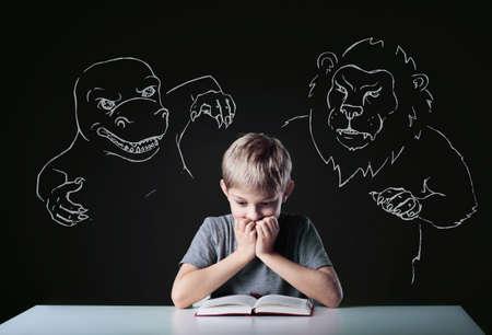 leon bebe: Ni�o peque�o asustado leer libro aterrador de monstruos