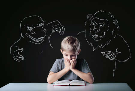 Scared little boy reading terrifying book about monsters photo