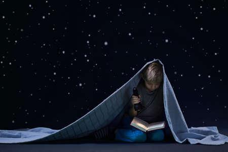Little boy reading book at night under the blanket Standard-Bild