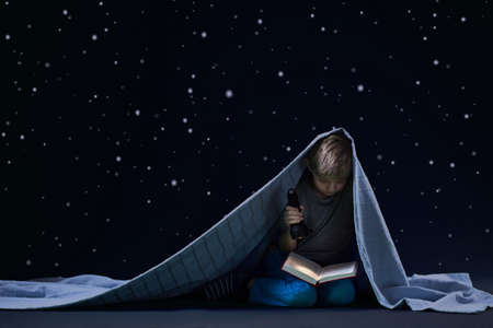night school: Little boy reading book at night under the blanket Stock Photo