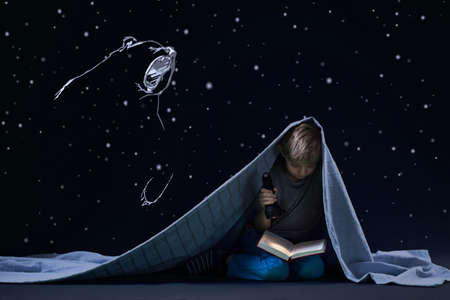 Little cute boy under quilt and his nights reading with torch