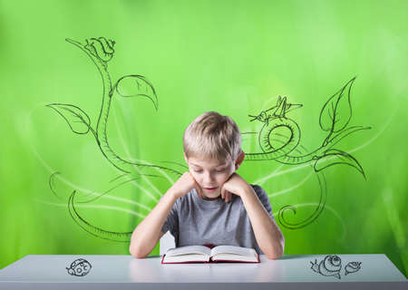 Excited little boy reading the book in green room photo