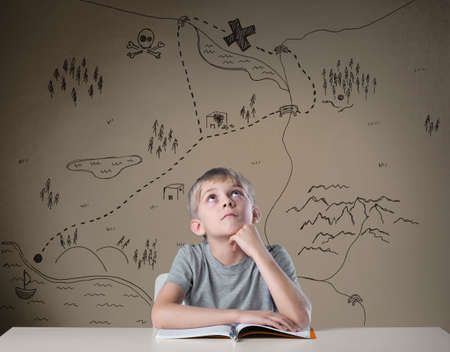 Little kid thinking about treasure map from his adventure book Imagens