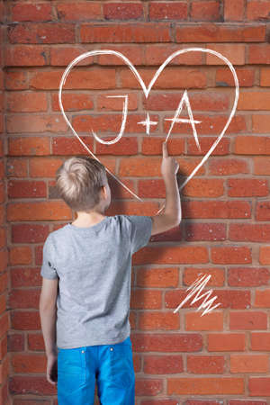 initials: Little boy in love drawing the heart with initials on wall
