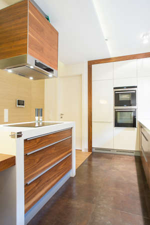 Vertical view of new luxury kitchen with wooden units photo
