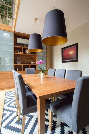 Image of eating room with wooden table and grey chairs Stock Photo