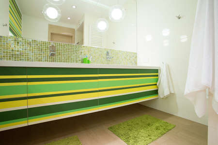 View of bright bathroom with green elements
