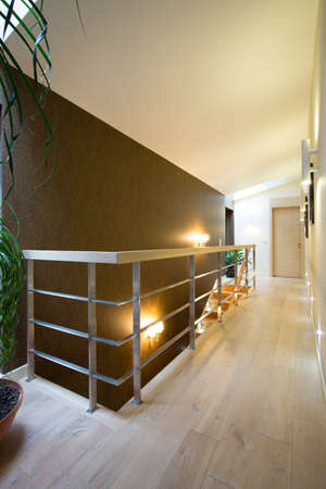 Vertical view of hallway with wooden floor and stairs
