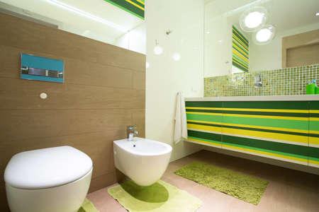 Big colorful bathroom with green units and marble floor Stock Photo