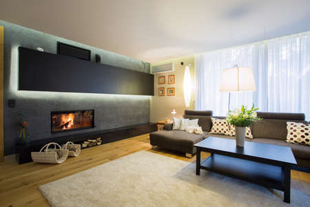 wooden furniture: Spacious living room with fireplace in wall