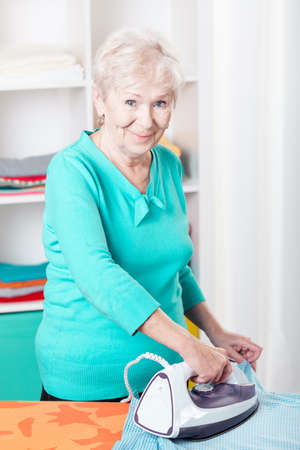 Elderly smiled woman ironing her clothes