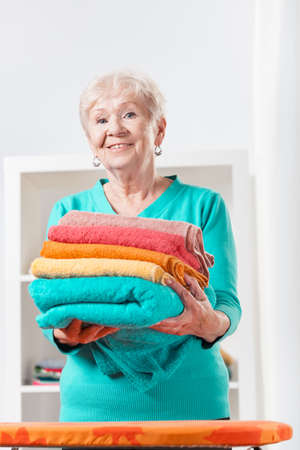 Aged smiled woman holding the clean towels