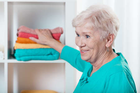 Aged nice lady putting clean towels to the closet