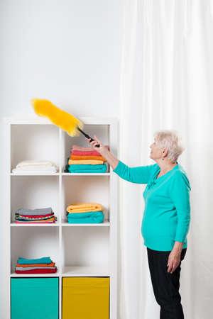 Elderly hardworking lady cleaning the shelfs
