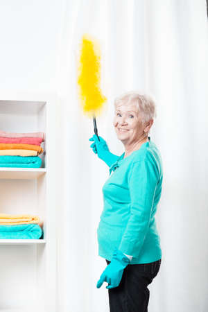 Aged smiled woman dusting the curtains in her dwelling