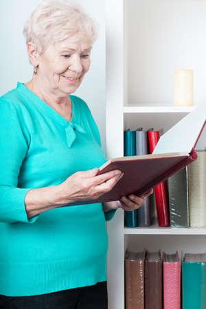 Older happy lady browsing the photo album Stock Photo