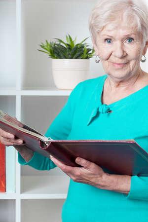 Old happy lady with photo album recalls good memories