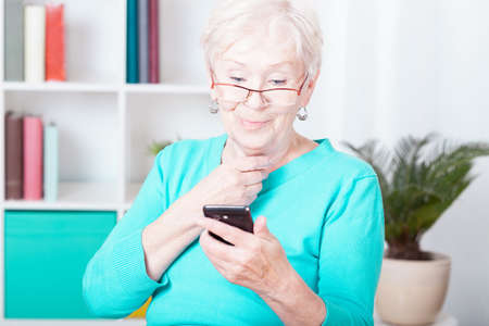 Older smiled lady and her new smartphone Stock Photo