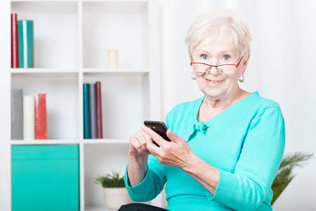 old cell phone: Picture of elderly woman using her smartphone