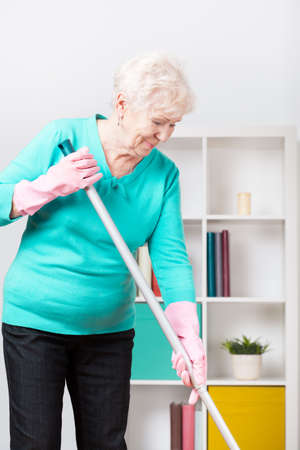 Aged happy woman doing her housework Stock Photo