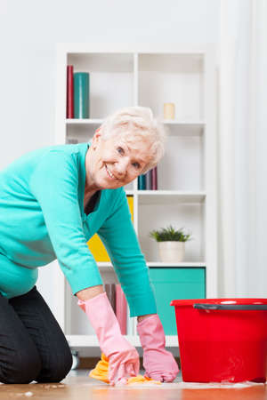 Active elderly lady cleaning the floor on her knees