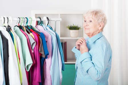 Older elegant lady dressing the shirt Stock Photo
