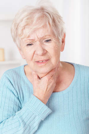Older sick woman with sore throat