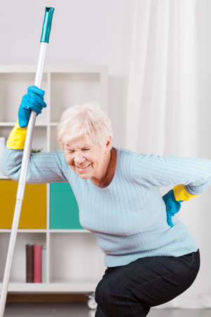 Elderly woman and terrible backache during cleaning up
