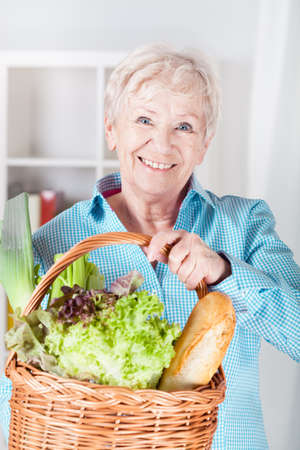 Smiling older woman with basket full of shopping