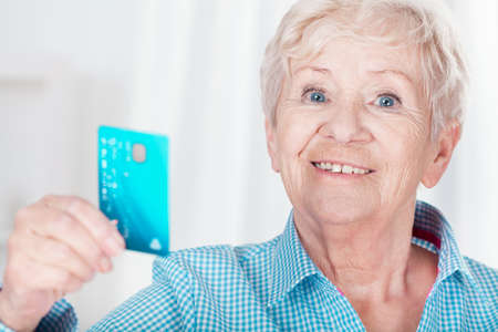 Aged happy woman holding her credit card