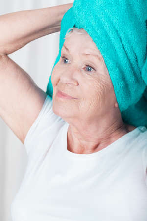 Older nice woman with towel on head after shower Stock Photo