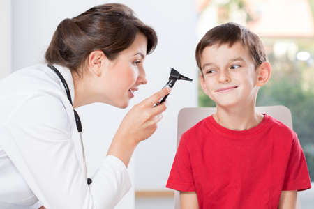 Young pretty doctor examinating little boy\'s hearing