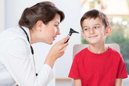 Joven médico bastante examinating audiencia del niño pequeño Foto de archivo - 38576763