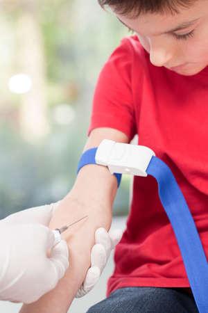 Brave little kid on his blood sampling at doctors cabinet