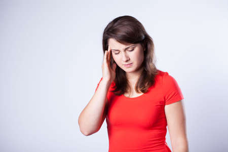 Young woman with headache on grey background